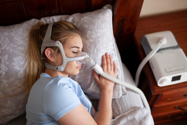 A woman sleeping while wearing a CPAP machine