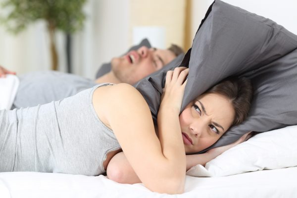 A woman holding a pillow over her ears while her husband snores